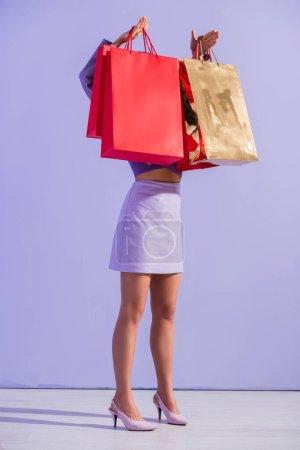 Foto de Mujer joven vestida con estilo de muñeca con bolsas de compras rojas sobre fondo de color violeta - Imagen libre de derechos