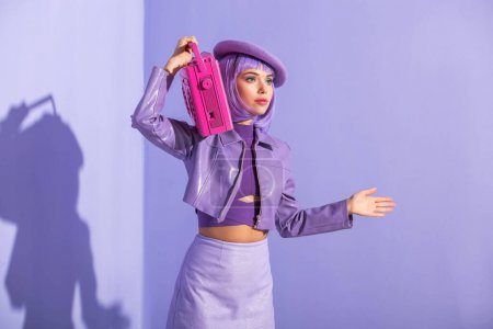 junge Frau im Puppenstil posiert mit rosa Retro-Tonbandgerät auf violett buntem Hintergrund