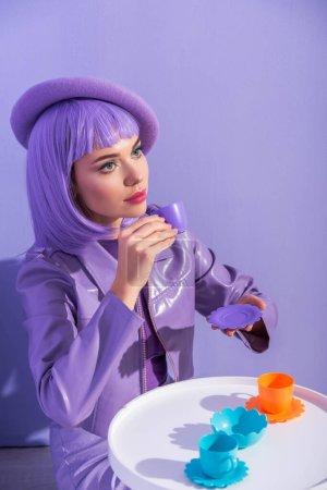 Photo pour Jeune femme vêtue de style poupée en béret posant avec des plats de jouets sur fond violet coloré - image libre de droit