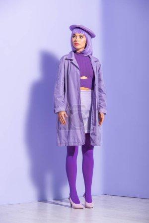 Photo pour Jeune femme habillée de style poupée en béret posant sur fond violet coloré - image libre de droit