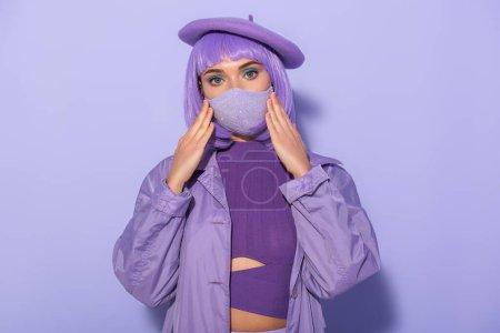 junge Frau im Puppenstil mit medizinischer Maske und Baskenmütze auf violettem Hintergrund