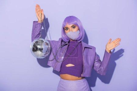 jeune femme habillée de style poupée en masque médical avec boule disco sur fond violet coloré