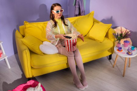Photo pour Jeune femme se faisant passer pour une poupée avec pop-corn et télécommande en 3d lunettes sur canapé jaune - image libre de droit