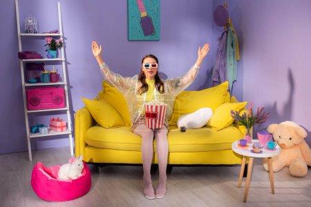 Photo pour Jeune femme se faisant passer pour une poupée avec du pop-corn dans des lunettes 3D sur un canapé jaune - image libre de droit