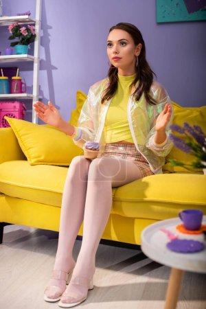 joven mujer posando como muñeca con cupcake en sofá amarillo