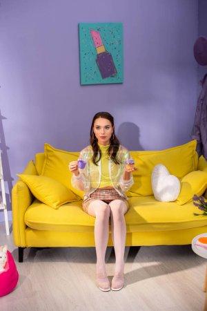 mujer joven haciéndose pasar por muñeca con cupcake y taza de juguete en el sofá amarillo