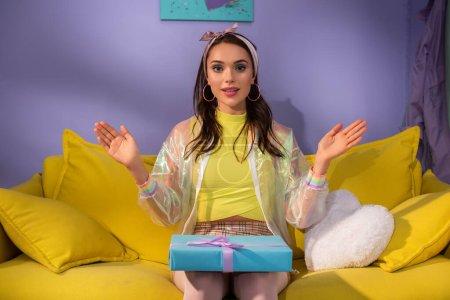 junge Frau posiert als Puppe mit Geschenkbox auf gelbem Sofa