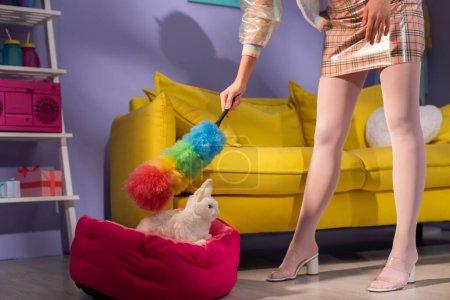 vue recadrée de jeune femme se faisant passer pour une poupée avec chiffon près du lapin jouet à la maison
