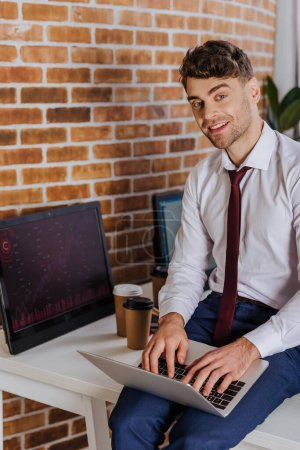 Photo for Smiling businessman using laptop near computer with charts and coffee to go on blurred background - Royalty Free Image