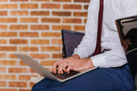 Photo pour Vue recadrée de l'homme d'affaires en utilisant un ordinateur portable près de l'ordinateur sur le premier plan flou - image libre de droit