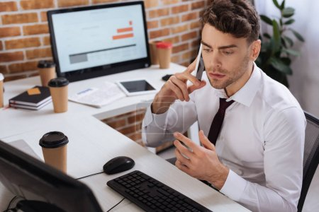 Businessman talking on smartphone near computer and coffee to go on blurred foreground