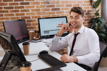 Photo for Smiling businessman talking on smartphone near computers with finance charts and takeaway coffee on blurred background - Royalty Free Image
