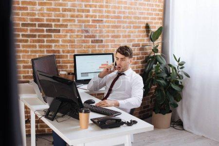 Photo pour Homme d'affaires incroyable parler sur smartphone tout en vérifiant les stocks financiers sur les ordinateurs - image libre de droit