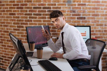 Geschäftsmann hält Smartphone in der Nähe von Kaffee-to-go-Anzeigencomputern mit Diagrammen auf dem Tisch