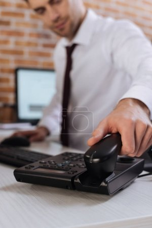 Cropped view of businessman on blurred background taking telephone handset
