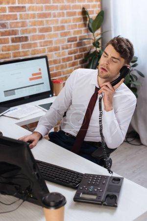 Photo pour Homme d'affaires parlant au téléphone près des ordinateurs et du café pour aller au premier plan flou dans le bureau - image libre de droit