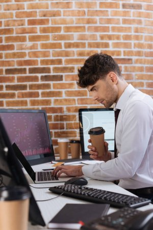 Businessman holding takeaway coffee and using laptop while checking financial stocks in office