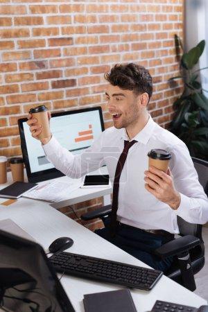 Photo pour Homme d'affaires positif avec café à emporter assis près des ordinateurs au premier plan flou - image libre de droit