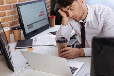 Photo pour Homme d'affaires fatigué tenant tasse de papier et vérifier les stocks financiers sur ordinateur portable sur le premier plan flou - image libre de droit