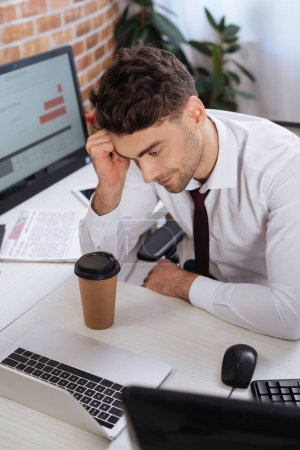 Young businessman looking at laptop while analyzing finance market in office
