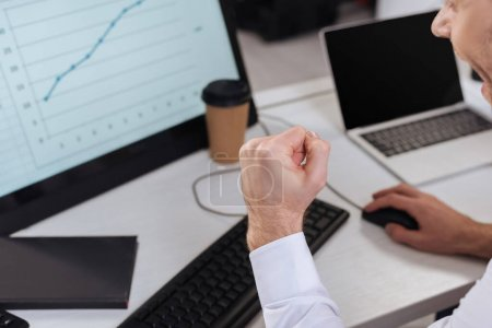 Cropped view of businessman showing yes gesture while using computer with chart on blurred background