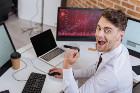 Excited businessman looking at camera while showing yeah gesture and checking financial courses on computer on blurred background
