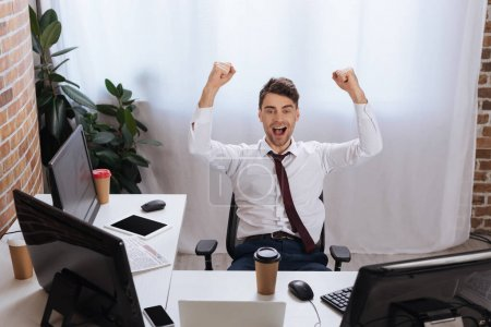 Photo for Excited businessman showing yeah gesture near computers, coffee to go and newspaper on blurred background - Royalty Free Image