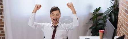 Photo for Excited businessman showing yeah gesture near computer and takeaway coffee in office, banner - Royalty Free Image