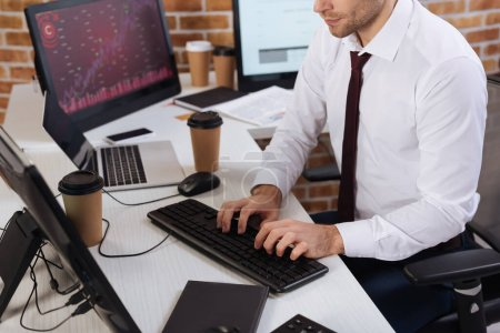 Cropped view of businessman using computer near coffee and notebook on blurred foreground