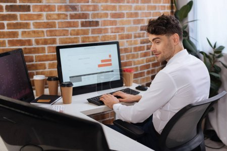 Businessman using computers while analyzing finance market near coffee to go in office