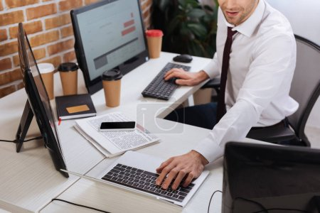 Photo pour Vue recadrée de l'homme d'affaires à l'aide d'un ordinateur portable et d'un ordinateur tout en vérifiant les stocks financiers près du smartphone et des nouvelles au bureau - image libre de droit