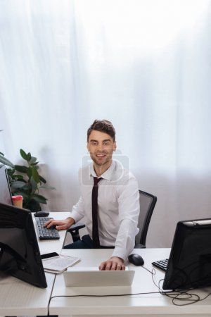 Smiling businessman using computers while checking finance market in office
