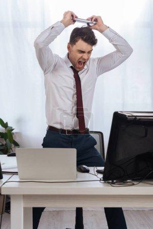 Photo pour Homme d'affaires fou criant tout en tenant un ordinateur portable près des ordinateurs sur le premier plan flou - image libre de droit
