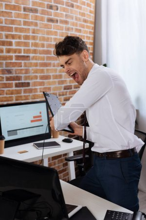 Photo pour Homme d'affaires fou tenant le clavier et criant près de l'ordinateur sur le premier plan flou - image libre de droit