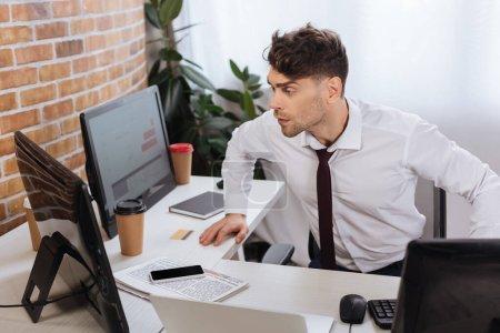 Photo pour Jeune homme d'affaires regardant l'ordinateur tout en vérifiant les stocks financiers près du smartphone et du journal sur la table - image libre de droit