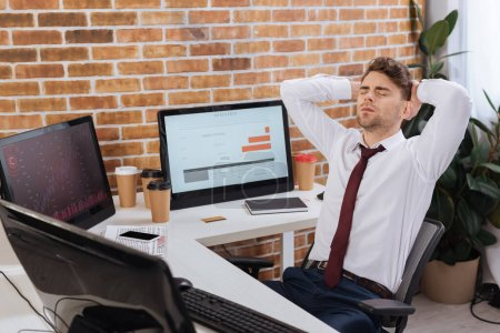 Photo for Exhausted businessman sitting near computers with charts of finance courses on monitor - Royalty Free Image