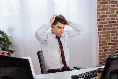 Photo pour Homme d'affaires stressé regardant l'ordinateur près du café pour aller sur le premier plan flou - image libre de droit