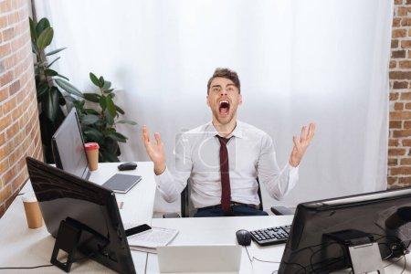 Photo pour Homme d'affaires fou criant près des appareils et du journal sur le premier plan flou sur la table - image libre de droit