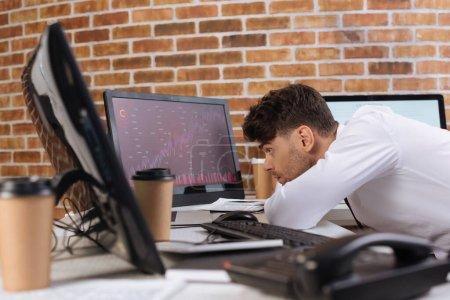 Photo pour Homme d'affaires concentré regardant l'ordinateur avec des cartes des stocks financiers sur moniteur près du téléphone et café à emporter sur le premier plan flou - image libre de droit