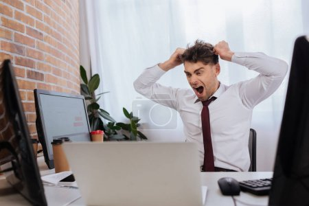 Photo pour Homme d'affaires en colère regardant les ordinateurs tout en analysant les cours numériques au bureau - image libre de droit