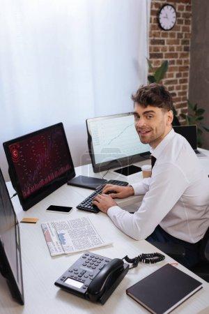 Photo pour Homme d'affaires souriant utilisant un ordinateur avec des cartes sur l'écran près du téléphone, des journaux et un carnet sur le premier plan flou - image libre de droit