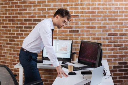 Photo pour Un homme d'affaires concentré vérifie les stocks financiers sur les ordinateurs de bureau - image libre de droit