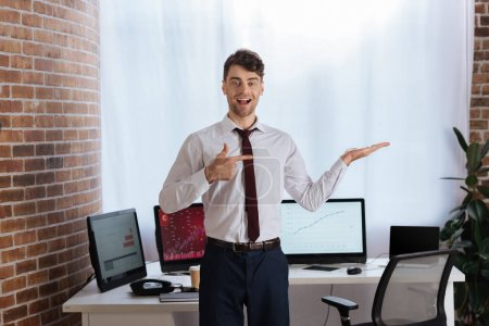 Photo for Smiling businessman pointing with hand and finger near computers on blurred background - Royalty Free Image