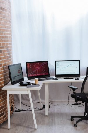 Computadoras con gráficos financieros en monitores cerca de tableta digital, café para llevar y teléfono en la mesa en la oficina