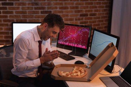 Podekscytowany biznesmen patrząc na pyszną pizzę w pobliżu komputerów z wykresami na rozmytym tle