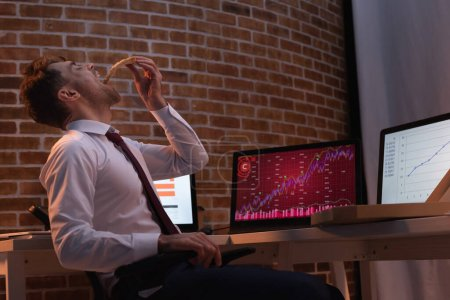 businessman eating takeaway pizza near computers with graphs on blurred background in office at evening