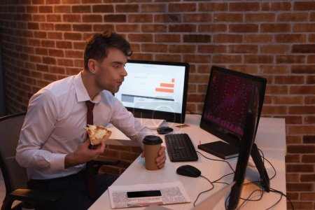 businessman eating pizza with takeaway coffee while checking stocks on computers in office