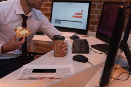 Photo pour Vue recadrée d'un homme d'affaires tenant une délicieuse pizza et un café pour s'approcher des ordinateurs, des nouvelles et du smartphone sur la table - image libre de droit