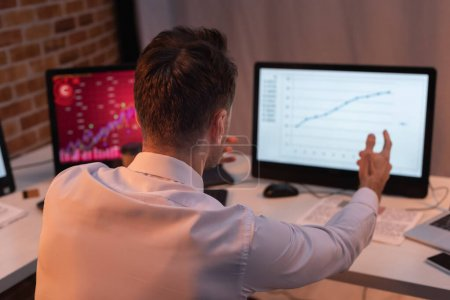 Back view of businessman pointing at computer with financial charts on blurred background