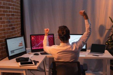 Photo pour Vue arrière de l'homme d'affaires montrant geste ouais près des ordinateurs et des appareils sur fond flou dans la soirée - image libre de droit